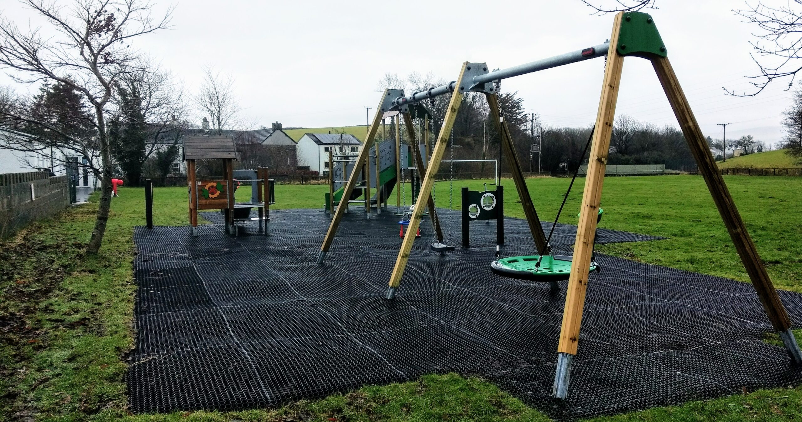 Swings in foreground of view of the play area